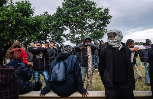 Migrants in Calais waited for a chance to run past the police to climb onto trains Thursday near the Channel Tunnel. Credit Tom Jamieson for The New York Times