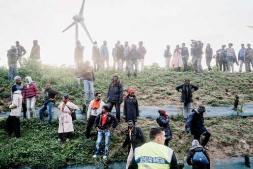 """Migrants in Calais. """"We come here because this is the only road to England,"""" a Syrian man said. Credit Tom Jamieson for The New York Times"""