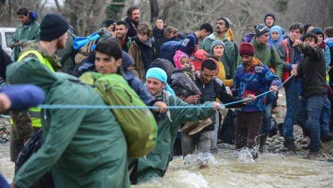 Refugees cross a river near Idomeni to enter Macedonia