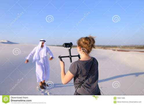 girl-shoots-camera-dancing-muslim-man-spacious-desert-h-process-shooting-arab-guy-camera-young-women-holds-camera-104211665